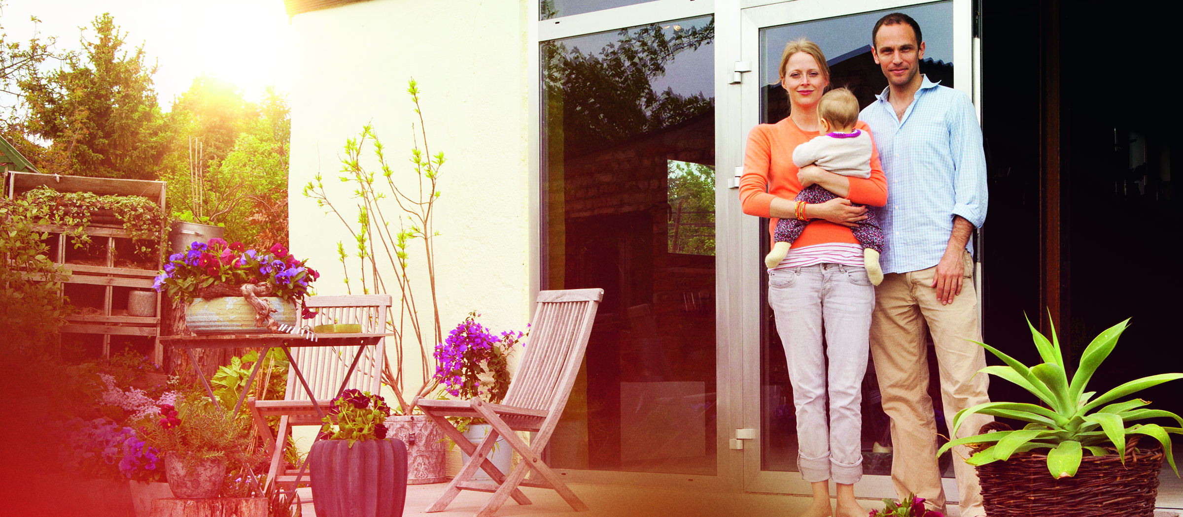 A man and a woman holding a baby standing on the patio in front of their house